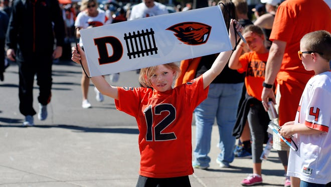 Keeley Grissom, 7, from Bend., Ore., cheers the Oregon State football team as they arrive for an NCAA college football game against San Jose State in Corvallis, Ore., Saturday, Sept. 19, 2015.
