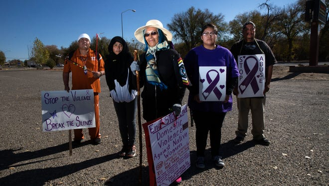 Ema Thompson, also known as Grandma Ema, center, stands with supporters, Efrem John, left, Cheyanne Arviso, Rhea Benally and her father Ouray D. Benally Thursday at the Shiprock Chapter House.