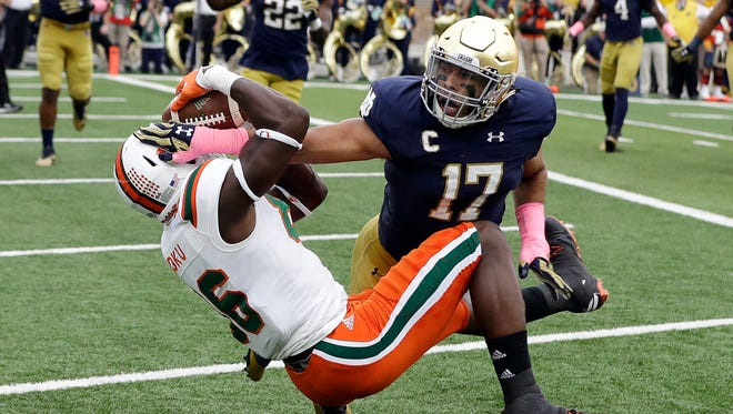 Miami 's David Njoku makes 2-yard touchdown reception while defended by Notre Dame's James Onwualu during the first half.