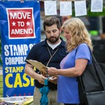 Michael Ippolito (left) of Move to Ammend, which seeks to overturn the Citizens United case, speaks with Chris Stock of Groton before the Neil Young at the Champlain Valley Expo in Essex Junction on Sunday, July 19, 2015.