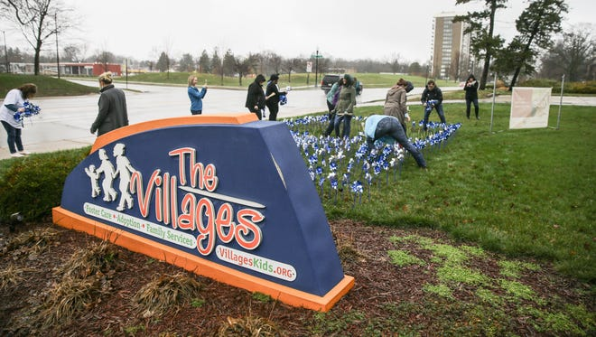 Volunteers and employees of The Villages Indiana and Prevent Child Abuse Indiana plant 1,000 pinwheels in front of their headquarters in Indianapolis on Thursday, March 29, 2018.