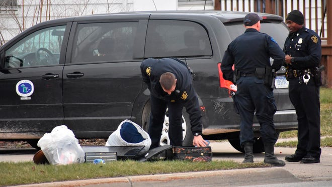 In this Wednesday, April 18, 2018 photo, officers investigate after two infant children were allegedly left in a suitcase along West Pierson Pierson Road in Flint, Mich.