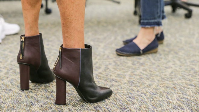 A survivor tries on boots during a personalized shopping experience with trained independent stylists from cabi women's clothing co. during the Benefit from Heart of cabi clothing donation event at the Julian Center in Indianapolis on Wednesday, May 16, 2018. New clothing shoes and jewelry are provided by the Benefit from Heart of cabi foundation and the stylists themselves.