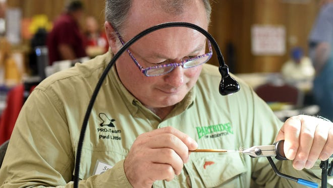 "Paul Little, 58, of the United Kingdom, ties a ""classic English spider"" Thursday at the 2015 Sowbug Roundup at the Baxter County Fairgrounds. More than 100 fly tyers from 25 states and two countries are showcasing their skills at the Sowbug this year, which runs through Saturday."