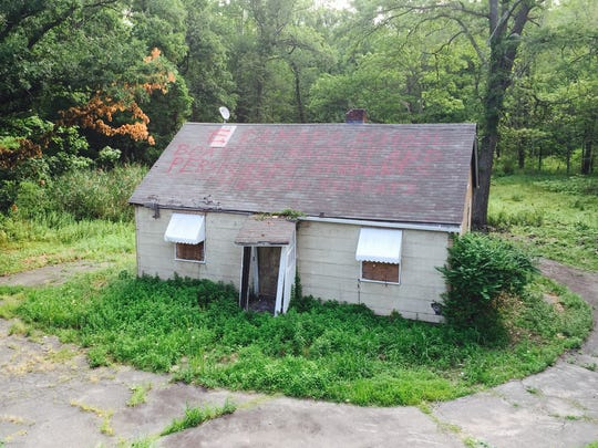 """""""E Ramapo School Board is racist and persecutes students History repeats,"""" reads the red message painted on the rooftop of the house in woods about 50 yards off Route 45 at Conklin Road in Pomona."""