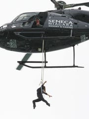 Nik Wallenda watches from above as his wife, Erendira Wallenda, hangs by her teeth while suspended from a helicopter above Niagara Falls in Niagara Falls, N.Y., Thursday, June 15, 2017.  The 36-year-old mother of three spent about eight minutes of the 10-minute stunt hovering over the falls.(AP Photo/Bill Wippert)