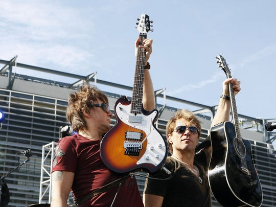 Richie Sambora and Jon Bon Jovi, right, hold up their guitars as they perform Thursday, Oct. 22, 2009, during an invitation only performance by Bon Jovi for 5,000 fan club contest winners and construction workers outside MetLife Stadium in East Rutherford.