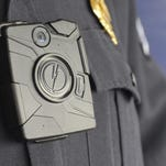 A body camera is worn by a police officer.