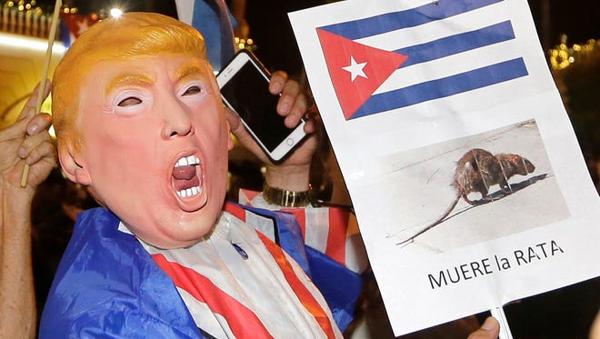 A person wearing a Donald Trump mask holds a sign in Spanish that reads the Rat Dies as he celebrates the death of Fidel Castro Nov. 26, 2016, in the Little Havana area in Miami.