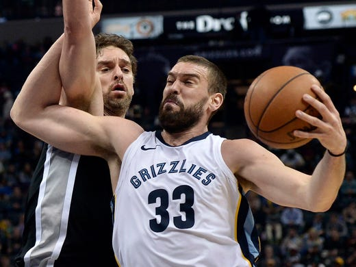 Memphis Grizzlies center Marc Gasol (33) drives against San Antonio Spurs center Pau Gasol during the first half of an NBA basketball game Wednesday, Jan. 24, 2018, in Memphis, Tenn. (AP Photo/Brandon Dill)
