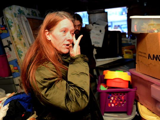 Stephanie Jezowski wipes a tear from her eye as she and her husband, Ted, stand in their garage and look through some of their children's belongings stored there. The Jezowskis lost their parental rights in court in 2014. They still keep many of their kids' clothes and toys.
