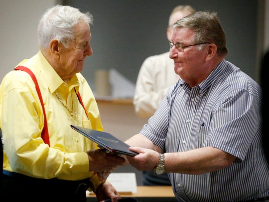 Edward Taylor, 89, left, shakes the hand of Elmira Heights Board of Education president Harry Blish while receiving a honorary high school diploma on Feb. 25.