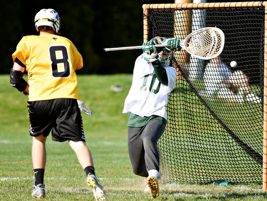 Red Lion's Nick Shima, left, shoots for a goal as York