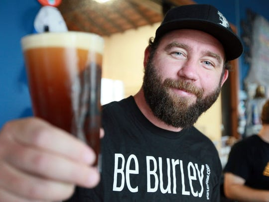 Burley Oak owner Bryan Brushmiller holds a glass of