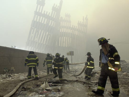 Firefighters work beneath destroyed mullions, the vertical