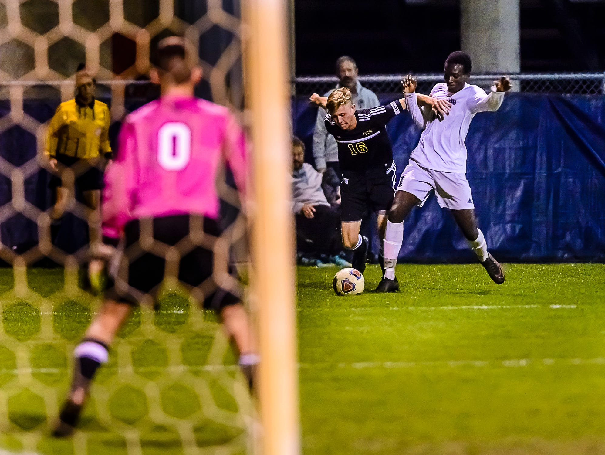 Hunter Nash ,16 of Haslett fights for position on the ball with Sam Lebbie ,right, of East Lansing as the Haslett goalie Dubs Westerland ,0, readies himself in the 1st half of their Gold Cup Final game Tuesday October 11, 2016 in Mason. KEVIN W. FOWLER PHOTO