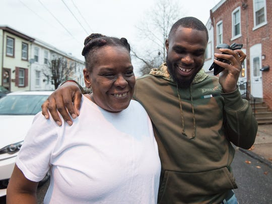 Eagles running back Wendell Smallwood, who grew up in Wilmington, talks with Shanell Butler on the phone as her mother, Francine Butler, listens after Wendell dropped off Christmas gifts.
