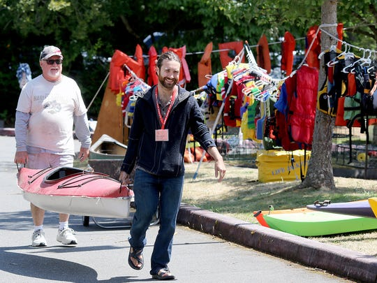 Tom and Benjamin Knight carry a kayak while helping set up for the Bainbridge Island Rotary and Rummage Sale on Monday at Woodward Middle School. The sale runs from 8 a.m. to 2 p.m. Saturday at Woodward, 9125 Sportsman Club Road. Donations can still be made from 8 a.m. to 8 p.m. Wednesday. For more information, go to www.bainbridgerotaryauction.org.