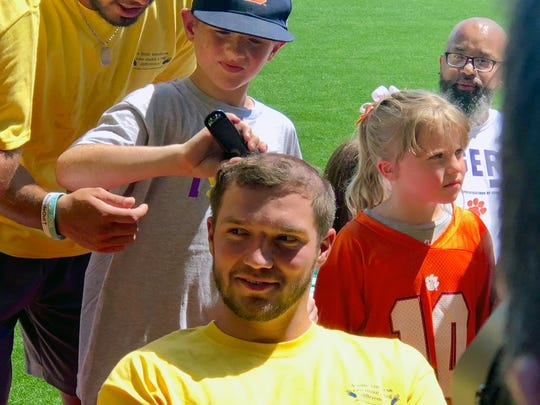 "Nine-year-old Hayden Long cuts Clemson kicker Greg Huegel's hair during Scott Pollard's ""All Off For Cancer"" charity event at Clemson's football complex on July 11, 2018."