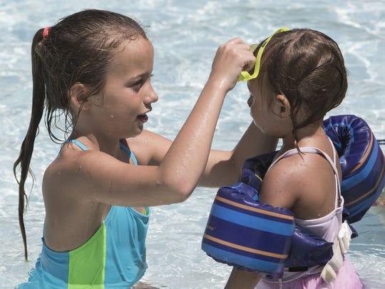 Aila Bowers, 8, puts swim googles on Hayden Bowers,