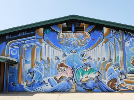 "This powerful 1998 Jose Ortiz mural on the side of the Natividad Elementary School is called Los Niños Cosmos (Cosmos Children) and exemplifies Ortiz' signature collaborative approach to art. Students, parents and faculty were asked their ideas and inspirations for a mural, and Ortiz, along with youth members of ""Hijos Del Sol"" and fellow artist Luis Cerna Jasso, wove them into a mythical tapestry where education, labor, and technology seamlessly contribute to a better world. The artists give special thanks to Ms. Patricia Gaglioti, Dr. Mark Schwartz, and Ms. Kary Shender."
