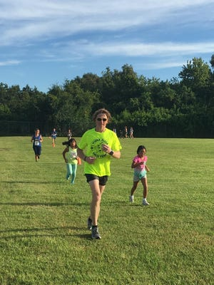 Howard Kanner runs with the kids during the youth race after the Running on Island Time 5K run in August.