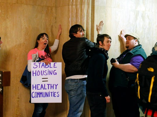 Protesters pound on the walls outside of the House Chamber in the Capitol Building, in Salem , Ore., on Thursday, Feb. 18, 2016. The group were protesting for a higher minimum wage, local control of rent control laws, and an end to Oregon Department of Transportation sweeps of homeless camps. (AP Photo/Timothy J. Gonzalez)
