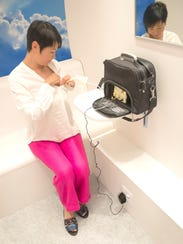 Woman pumping breast milk in a Mamava pod.