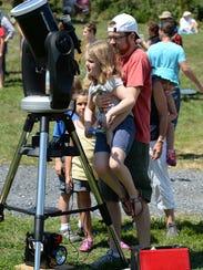 Ben Wiesehan holds daughter Hazel up to a telescope