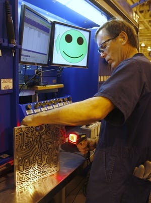 A worker inspects a control unit for a transmission being built at Ford's Sharonville plant.