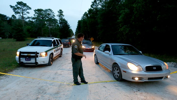 A Gilchrist County, Fla., sheriff's deputy lowers the yellow tape to let vehicles through at the scene of a shooting on Thu