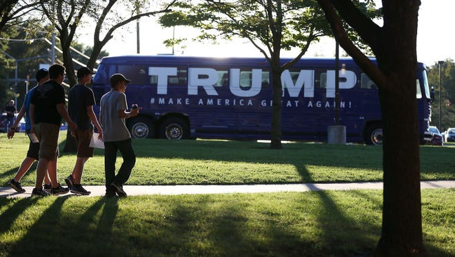 A group of people walk past a Donald Trump campaign bus parked outside of Urbandale High School on Saturday, Sept. 19, 2015, where presidential candidate Donald Trump gave a speech.