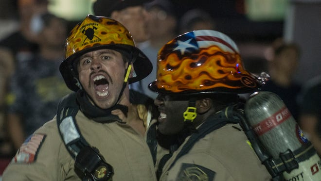 Montgomery firefighter Christian De Alba, left, reacts to winning the world championship. The Montgomery Fire DepartmentÕs Blue Team, which broke the world-record with a time of 1:05.54 on the relay this week, won the world championship Saturday. The 2015 Scott World Firefighter Combat Challenge XXIV finals were Saturday, Oct. 24, 2015, in downtown Montgomery, Ala.