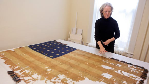 Conservator Nancy Love works with one of two flags