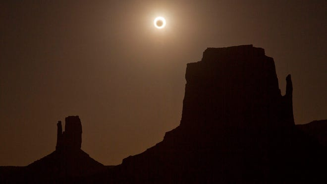 In this May 20, 2012, file photo, the new moon crosses in front of the sun creating an annular eclipse over West Mitten, left, and East Mitten buttes in Monument Valley, Ariz.