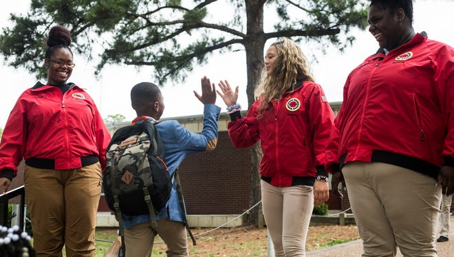 May 18, 2017 - Claudia Raines high fives a student as he arrives at Brownsville Elementary school. City Year is a Americorps program that supports schools in poor areas and is wrapping up its first year in Memphis. The program employs recent college graduates to work in support roles in schools, focusing on issues like attendance and behavior.