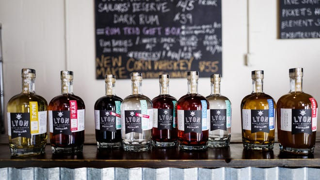 Bottles of rum, whiskey and orange liqueur line the Lyon Distilling Company's tasting room table.