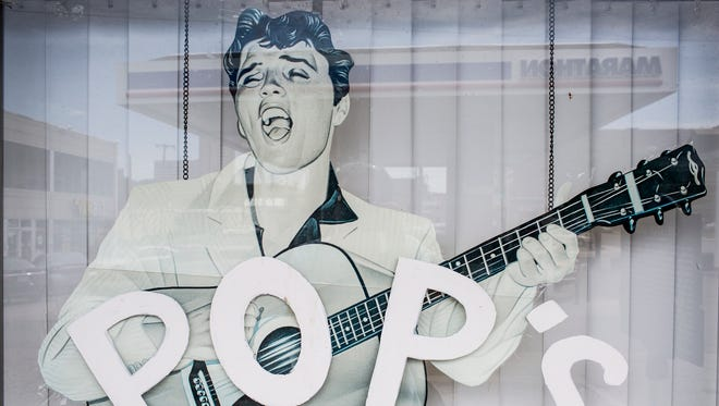 An Elvis Presley cardboard cutout is seen through a window June 15, 2017, at ASAP Bail Bonds, which used to be Poplar Tunes. Elvis, who lived nearby, bought his first record in the old record store.