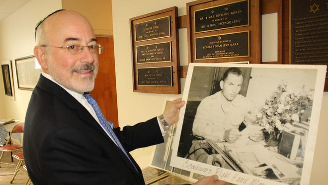 Ronnie Leet holds an enlarged photo of Seymour Cohn at Temple Mishkan Israel in Selma. Cohn was an Army Air Force officer in northern Africa during World War II. Funeral services were held for him Friday. Cohn died last week at the age of 102. Alvin Benn/Special to the Advertiser