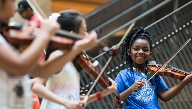 June 27, 2018 -  Danity Collins, 8, smiles after finishing a performance with the Harmonic South String Orchestra in the Crosstown Concourse Central Atrium on Wednesday.