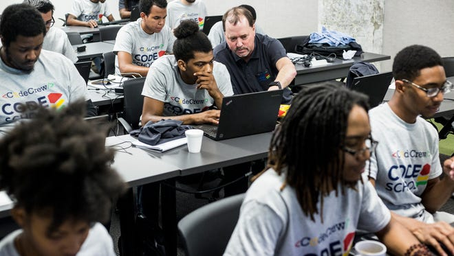 Caleb Canada receives help from teacher Kevin Yancy during Code Crew's new Code School on July 20, 2018, at Crosstown Concourse.