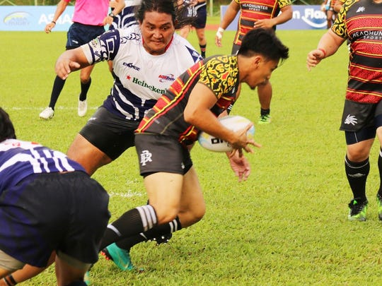 Johnny Borja about to tackle a Brunei back.