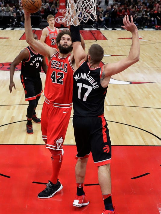 Chicago Bulls' Robin Lopez (42) shoots over Toronto Raptors' Jonas Valanciunas during the first half of an NBA basketball game Wednesday, Jan. 3, 2018, in Chicago. (AP Photo/Charles Rex Arbogast)