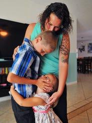 Deeanna Thomas of Melbourne hugs son Christian McPhilamy,
