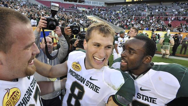 Kirk Cousins and Trenton Robinson celebrate together after the Spartans' 33-30 triple-overtime win over Georgia at the Outback Bowl in Tampa, Florida on Jan. 2, 2012.