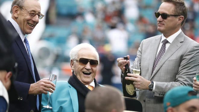 Dolphins owner Stephen Ross, left, toasts, former coach Don Shula, during a halftime celebrating the 1972 undefeated team in 2019. At the right is CEO Tom Garfinkel.