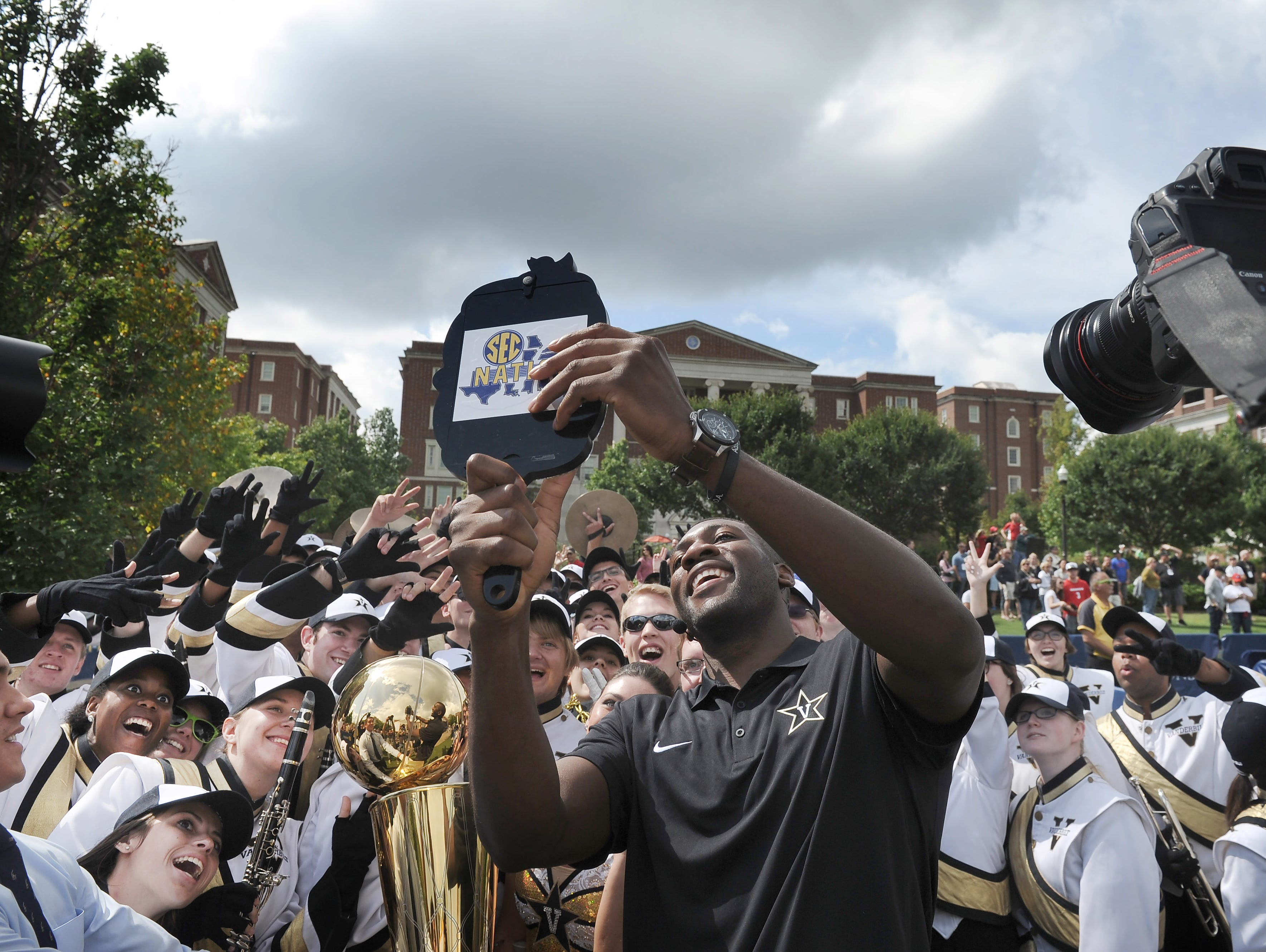 "Former Vanderbilt basketball star Festus Ezeli, of the Golden State Warriors, takes a selfie with the NBA Championship Trophy and the Vanderbilt band during the ""SEC Nation"" show at Vanderbilt on Saturday, Sept. 12, 2015."