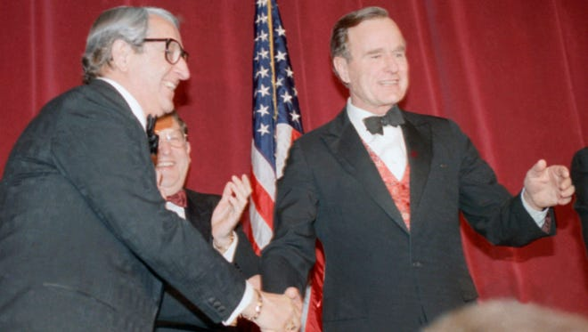 President George H. W. Bush gestures as he paid a drop-by on Saturday, March 18, 1989 in Washington at a St. Jude's Children's Research Hospital charity dinner in honor of  White House Chief of Staff John Sununu, standing center. At left is actor Danny Thomas, who is active in the St. Jude's Hospital charities.
