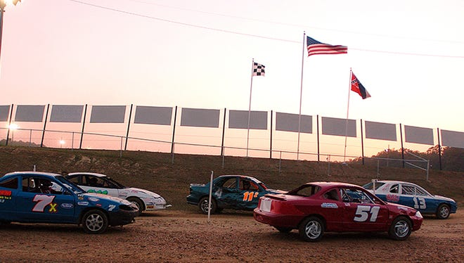 Drivers line up for their turns around the track as twilight settles over the Jackson Motor Speedway in Byram, Miss.