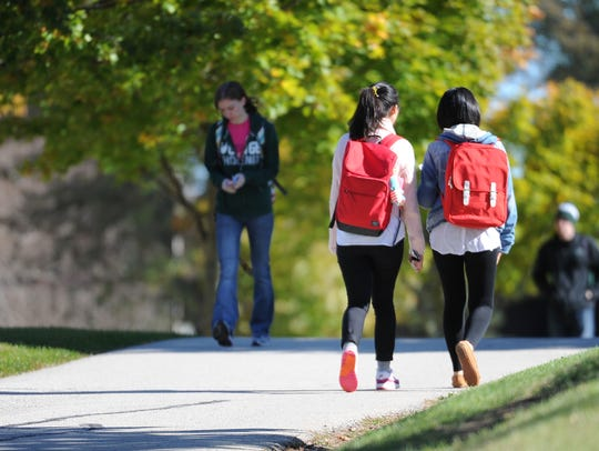 Students walk to the campus housing area at the University